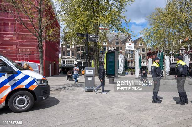 Dutch police officers stand guard the Leidseplein as Mayor Femke Halsema has issued an emergency ordinance the surrounding areas to keep the terraces...