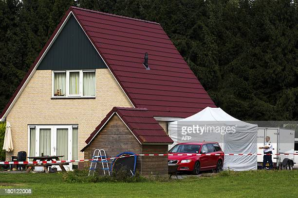 Dutch policeman arrives to inspect a crime scene in a bungalow, where the bodies of a man and his three children were found in a suspected...