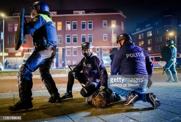 Dutch policemen arrest a man during clashes with a large group of young people on Beijerlandselaan in Rotterdam, on January 25, 2021. - The...