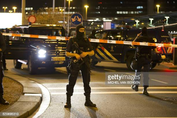 TOPSHOT Dutch policemen stand guard by a cordoned off area outside Amsterdam's Schiphol Airport late on April 12 after it was partially evacuated...