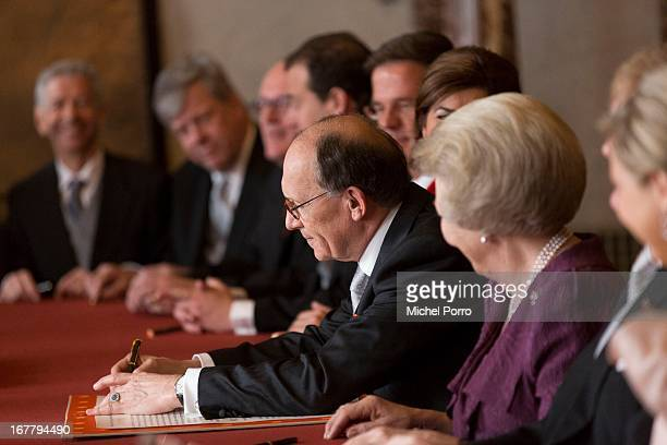 Dutch President of the Senate Fred de Graaf signs the Act of Abdication as Queen Beatrix of the Netherlands looks on in the Moseszaal at the Royal...