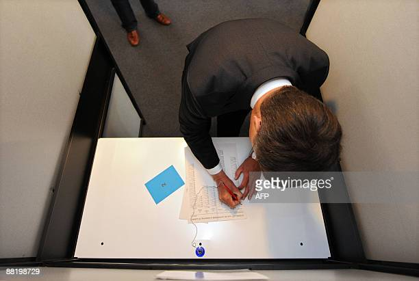 Dutch Prime Minister Jan Peter Balkenende stnds in a voting booth in the Dutch city of Capelle aan den IJssel on June 4 2009 during the European...