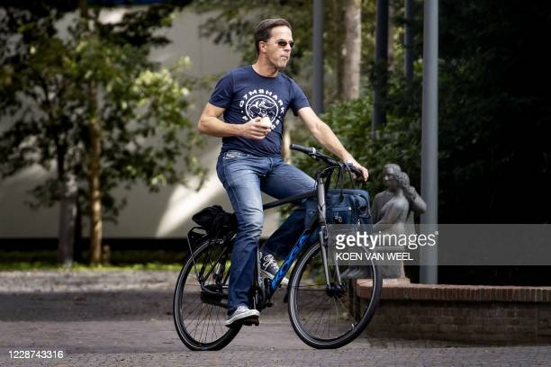 Dutch Prime Minister Mark Rutte arrives on a bike at the Catshuis for an informal meeting about Covid-19, in The Hague, on September 27, 2020. /...