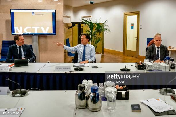 Dutch Prime Minister Mark Rutte gestures past Dutch Health Minister Hugo de Jonge and Dutch Minister of Justice and Security Ferd Grapperhaus during...
