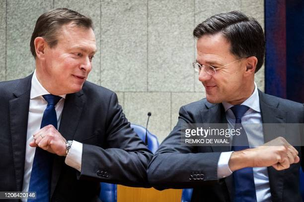 TOPSHOT Dutch Prime Minister Mark Rutte gives Dutch Minister for Medical Care Bruno Bruins an elbow greeting in order to prevent the spread of the...