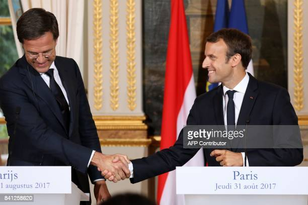 Dutch Prime Minister Mark Rutte shakes hands with French President Emmanuel Macron during a joint press conference following a meeting at the Elysee...