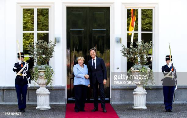Dutch Prime Minister Mark Rutte shakes hands with German Chancellor Angela Merkel prior to a working lunch on climate change at the Catshuis in The...