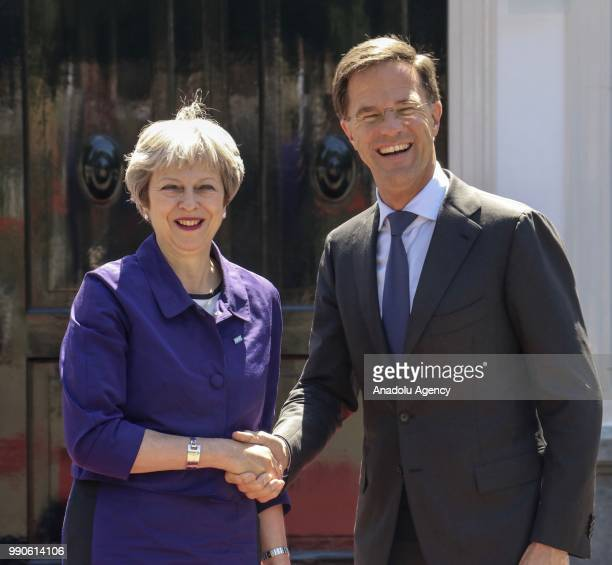 Dutch Prime Minister Mark Rutte shakes hands with his British counterpart Theresa May while they pose for a photo before a work lunch at the Catshuis...