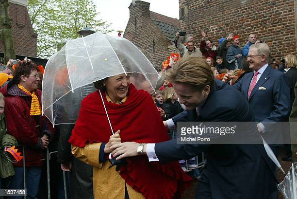 Dutch Prince Pieter Christiaan ducks under the umbrella of his mother, Princess Margriet, the sister of Queen Beatrix, during the celebrations for...