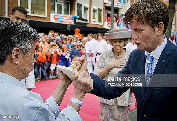 Dutch Prince PieterChristiaan attempts to break a wooden plank in two as Princess Beatrix looks on during the King's Day celebrations in Amstelveen...