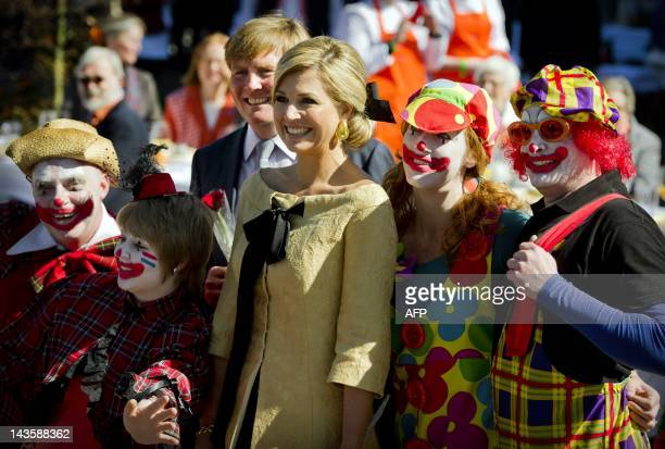 Dutch prince Willem Alexander and his wife princess Maxima pose with people dressed as clowns in Rhenen Netherlands on April 30 during the Queens Day...