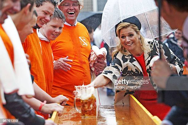 Dutch princess Maxima pulls beer glasses over the shuffleboard during the Queen's Day festivities, in Wemeldinge, on April 30, 2010. The Netherlands'...