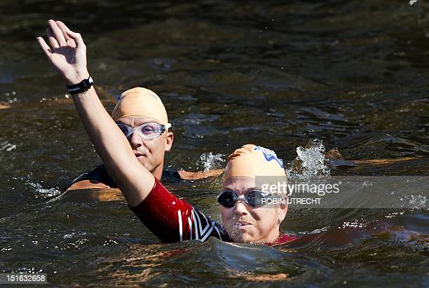 Dutch princess Maxima swims through a canal of Amsterdam on September 9 and waves as she takes part in the Amsterdam City Swim a charity event...