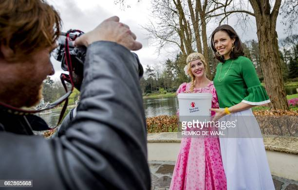 Dutch Princess Viktoria de Bourbon de Parma poses with a woman dressed as Cinderella before collecting coins from the Wensbron at Efteling amusement...