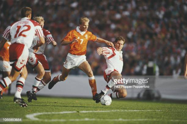 Dutch professional footballer Dennis Bergkamp forward with AFC Ajax pictured in action with the ball for the Netherlands team as Danish players...