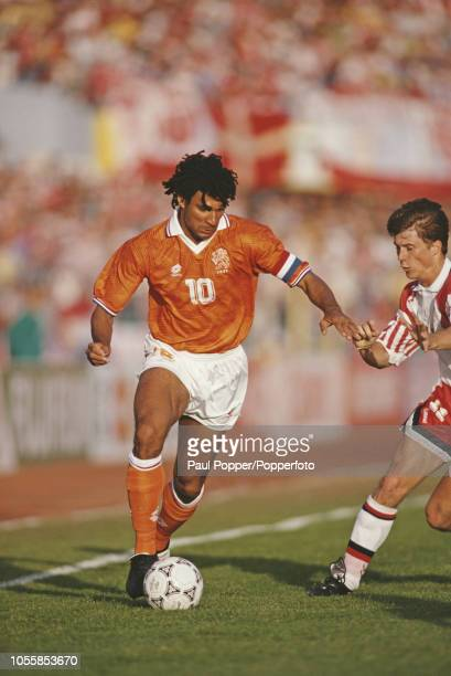 Dutch professional footballer Ruud Gullit midfielder/forward with AC Milan pictured making a run with the ball for the Netherlands team past Danish...