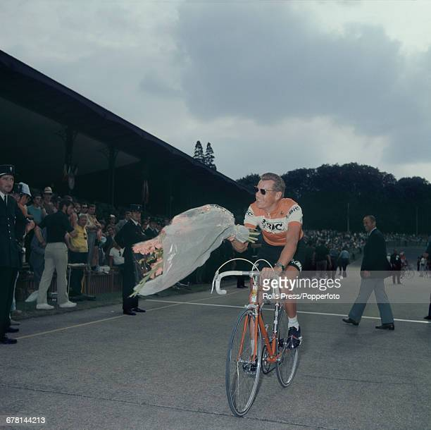Dutch professional road race cyclist Jan Janssen pictured cycling with a large bouquet of flowers after finishing in tenth place after completing the...