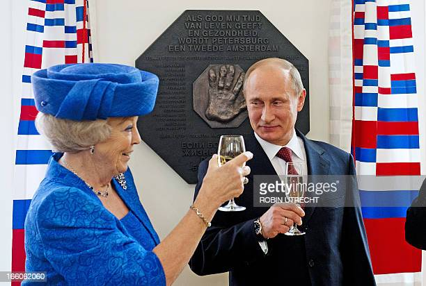 Dutch Queen Beatrix and Russian President Vladimir Putin raise their glasses after they unveiled a plaque during their visit at the Hermitage Museum...