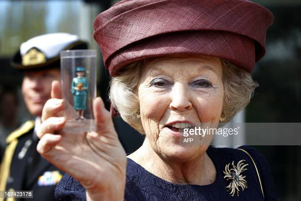 Dutch Queen Beatrix shows a miniature of herself during the opening of the renovated Madurodam in The Hague The Netherlands on April 21 2012 AFP...