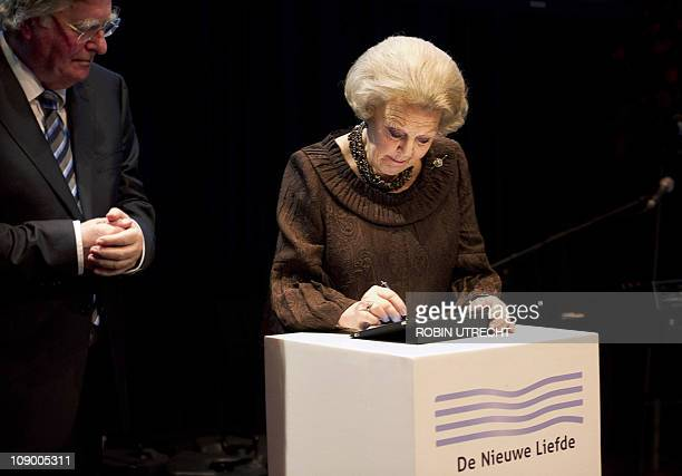 Dutch Queen Beatrix signs a digital guestbook on an iPad during the opening of a new center in Amsterdam The New Love on February 11 2011 The New...