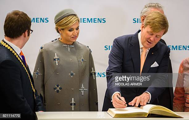 Dutch Queen Maxima AND C and King WillemAlexander sing a guest book during a visit at Siemens Healthcare complex on April 14 2016 in Erlangen The...