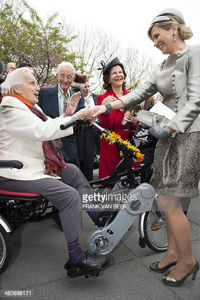 Dutch Queen Maxima and Sweden's Queen Silvia speak with people as they visit the nursing home 'The Hogeweyk'in Weesp The Netherlands on April 4 2014...