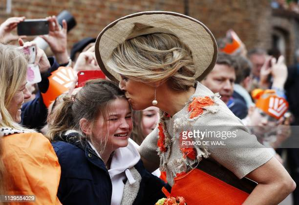 Dutch Queen Maxima kisses a girl on the head as she and her husban visit Amersfoort on Kings Day April 27 to mark King Willem-Alexander's birthday in...