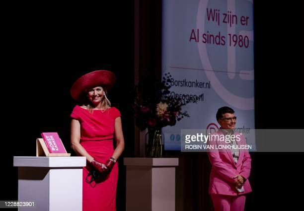Dutch Queen Maxima smiles as she receives the book 'Everything about breast cancer' during the opening of the annual breast cancer month during a...