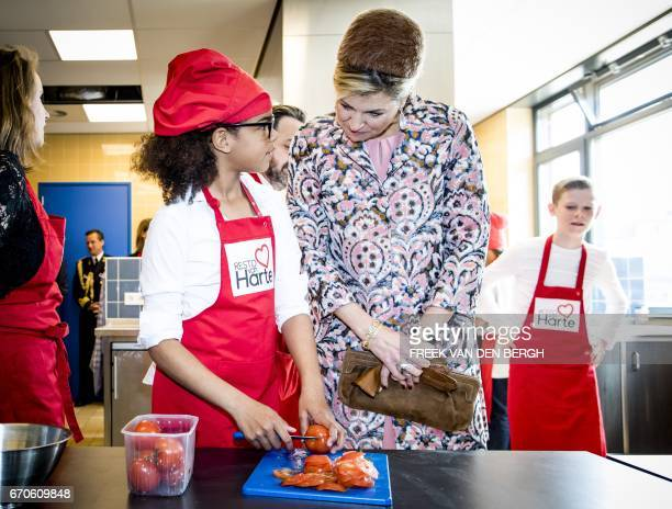 Dutch Queen Maxima watches a child cutting tomatoes during the opening of the fiftieth Resto VanHarte in Lelystad on April 20 where children can come...
