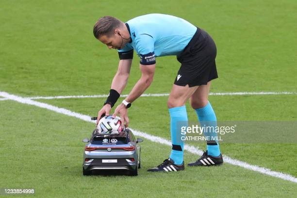 Dutch referee Danny Makkelie takes the ball from the remote control car ahead of the UEFA EURO 2020 semi-final football match between England and...