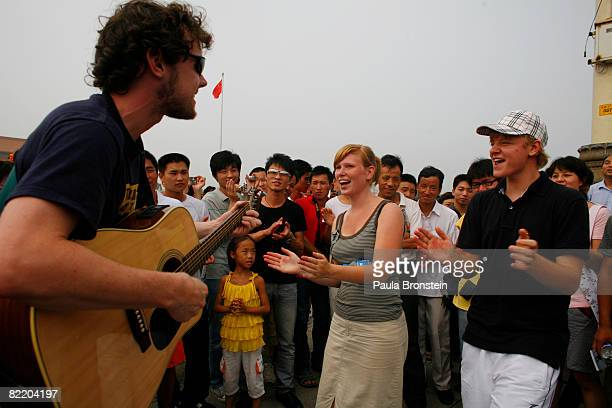 Dutch religious group sings songs in their native language as Chinese gather to listen in Tianamen square one day before the opening of the Beijing...