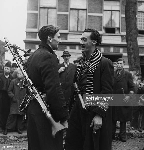 Dutch Resistance fighters armed with captured German weapons smoke and talk to each other on the street during liberation, Breda, Netherlands, 1944.
