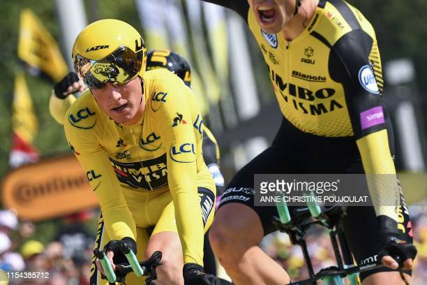 Dutch rider Mike Teunissen wearing his overall leader's yellow jersey and a teammate of Netherlands' Jumbo-Visma cycling team react as they win on...