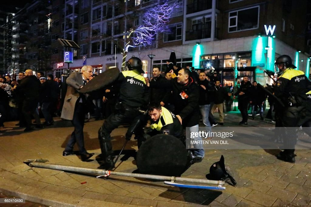 Dutch riot police clash with protesters near the Turkish consulate in Rotterdam on March 11, 2017 after the Turkish Family Minister was barred by police from entering the Turkish consulate and escorted out of the country. Turkey's Family Minister Fatma Betul Sayan Kaya was back in Istanbul after being expelled from the Netherlands and escorted back to Germany by Dutch police, condemning The Hague's 'ugly' treatment. / AFP PHOTO / ANP / Marten van Dijl / Netherlands OUT