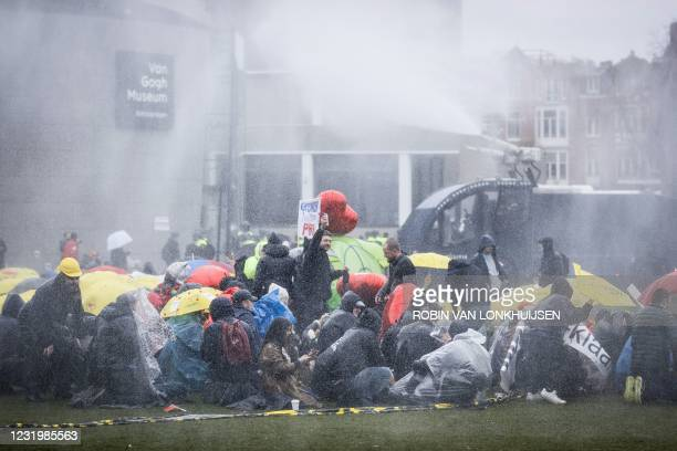 Dutch riot police intervenes with a water cannon as protesters gather on the Museumplein for the so-called Coffee Drink campaign to denounce the...