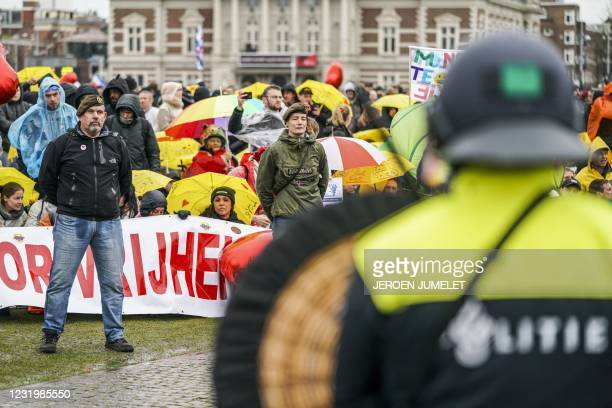 Dutch riot police watch campaigners in military clothing as they gather with protesters on the Museumplein for the so-called Coffee Drink campaign to...