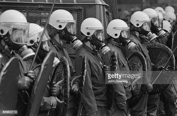 Dutch riot police with shields helmets and gasmasks during rioting by anarchist and antimonarchy protestors in Amsterdam on the day of the...