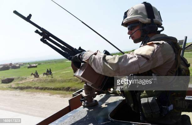 A Dutch soldier stands guard at his vehicle on a road to the airport to Ali Abad district of Kunduz province on April 7 2013 The Dutch have 500...