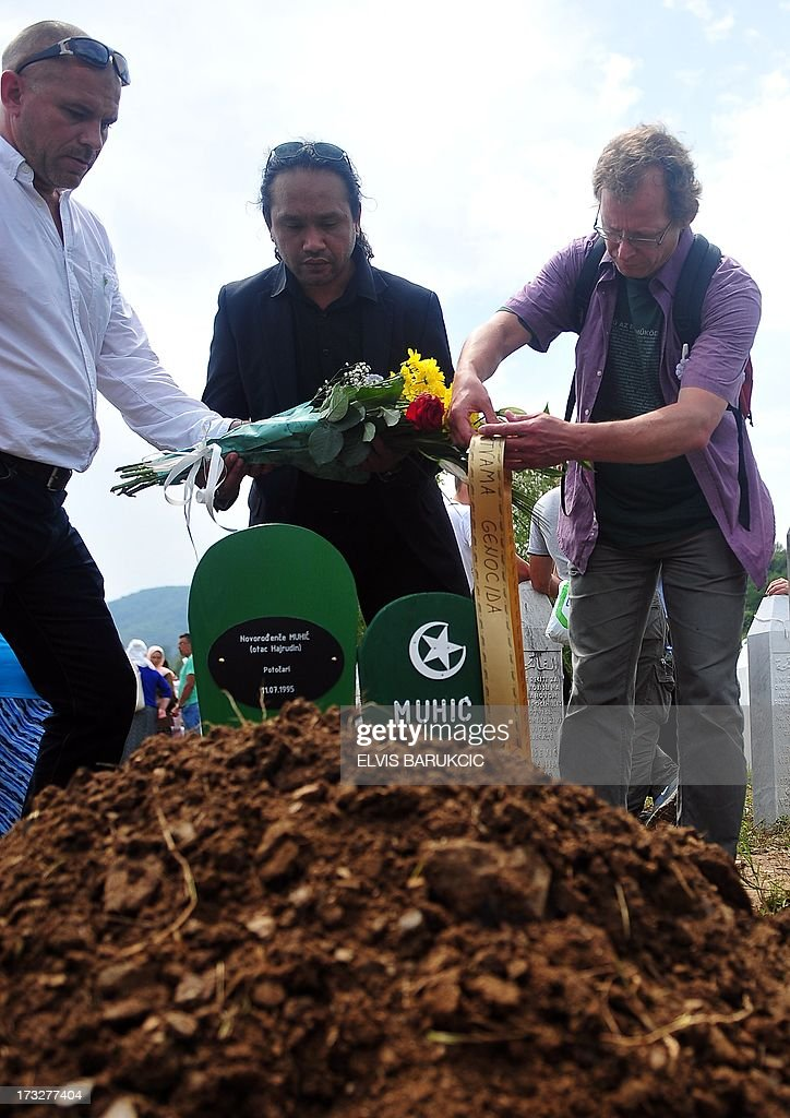 Dutch soldiers, ex-members of the UN mission to the 'Safe enclave of Srebrenica', Adje Anakotta (C), Dion Vandenberg (R) and Dave Maat (L), lay flowers on the freshly made grave of the youngest victim of Srebrenica 1995 massacre during a mass burial at a memorial cemetery in the village of Potocari near the eastern Bosnian town of Srebrenica on July 11, 2013. Bosnia buried 409 victims of the Srebrenica massacre on July 11, including a newborn baby, on the 18th anniversary of the worst slaughter in post-war Europe. More than 15,000 people travelled to Potocari, near Srebrenica to attend the mass funeral of victims whose remains were found in mass graves and only identified almost two decades after the 1995 killing.