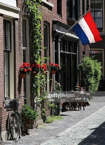 A Dutch street scene with a bike, flowers, chairs and a flag