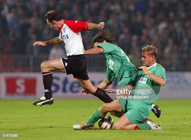 Dutch striker Bart Goor of Feyenoord and his Hungarian opponents Sorin Botis and Gabor Gyepes of Ferencvaros fight for the ball in 'Puskas' stadium...