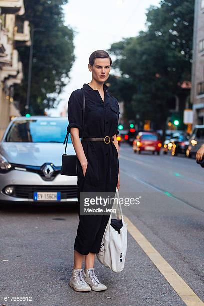 Dutch supermodel Saskia de Brauw wears a cropped black jumpsuit with a thin belt and a small black Celine purse after the Prada show during Milan...
