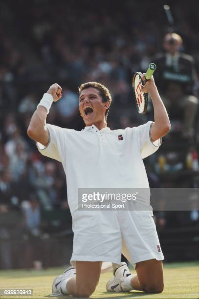 Dutch tennis player Richard Krajicek pictured holding his arms in the air in triumph as he kneels on the court after defeating American tennis player...