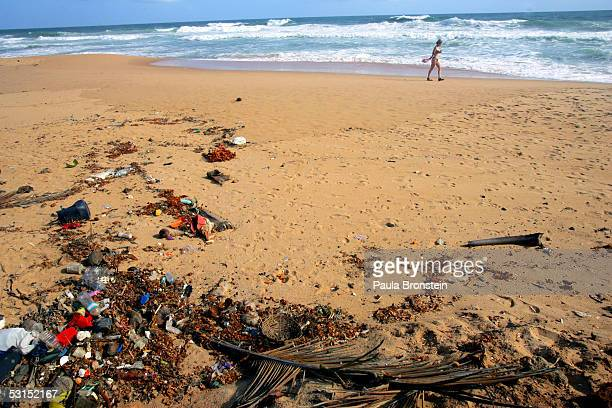Dutch tourist walks along the garbage strewn empty Hikkaduwa beach June 26 2005 in Hikkaduwa Sri Lanka Sri Lanka which depends on its income from...