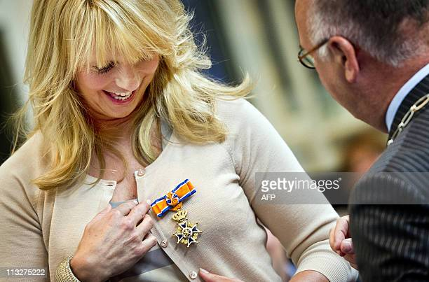 Dutch TV Hostess and actress Linda de Mol is promoted to Officer of the Order of OrangeNassau as Deputy Mayor Fons Hertog of Huizen gives her the...