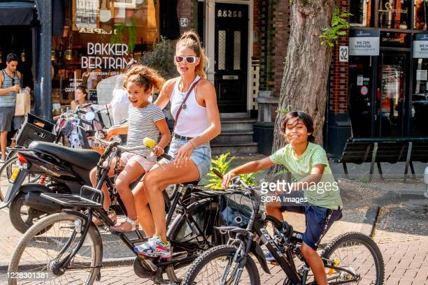 Dutch Victoria secret model Doutzen Kroes rides on the street with her children Myllena and Phyllon during the coronavirus crisis.