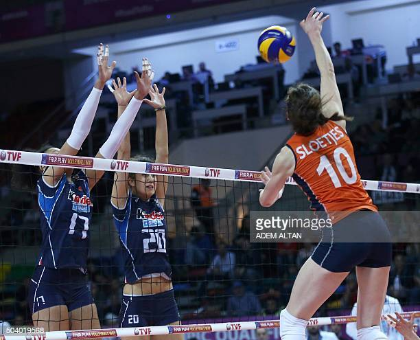 Dutch volleyball player Lonneke Sloetjes smashes as Italian players Valentina Diouf and Anna Danesi attempt to block during the European Olympic...