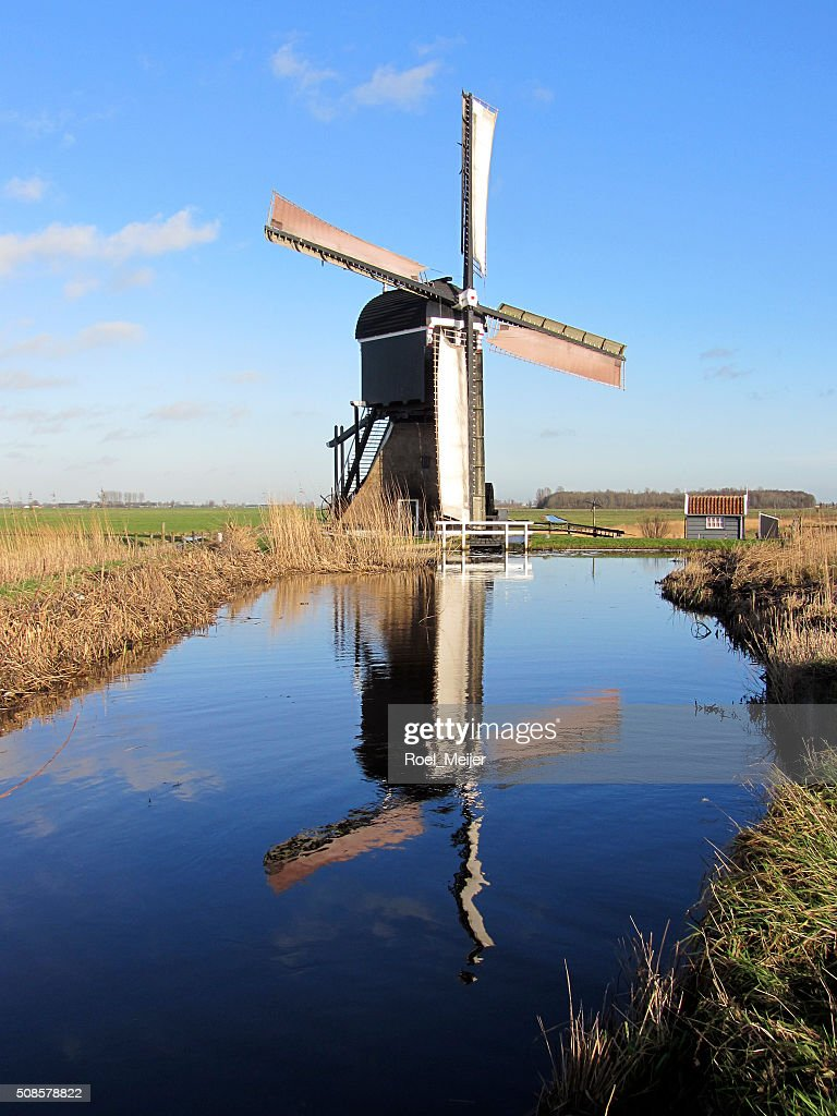 Dutch windmill reflected in water : Stock Photo