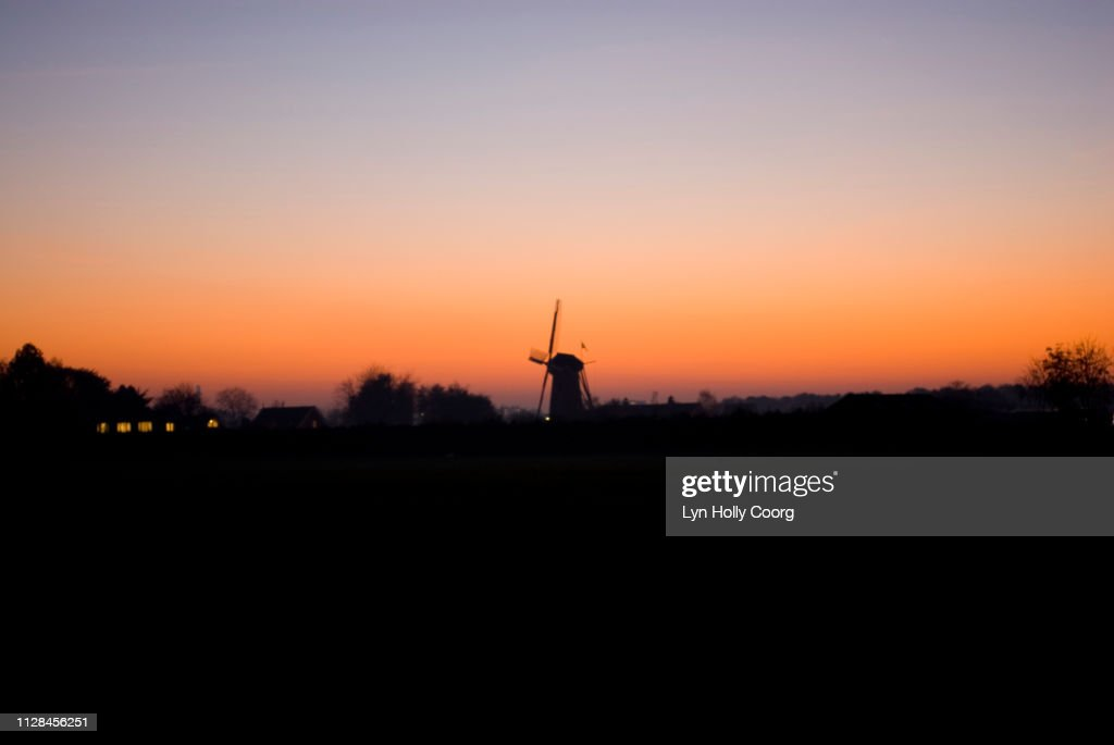 Dutch windmill silhouetted against horizon at sunset : ストックフォト