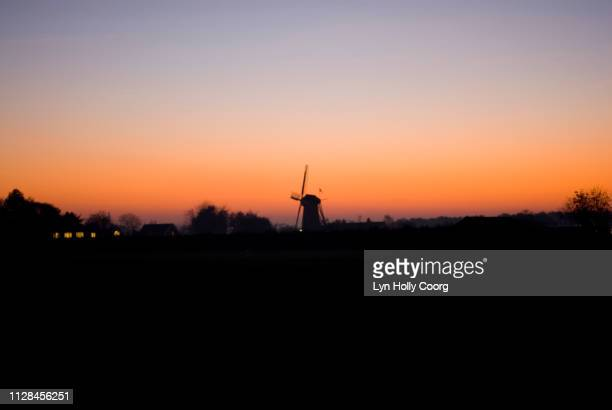 dutch windmill silhouetted against horizon at sunset - lyn holly coorg stock photos and pictures